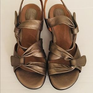Clark is artisan twisted golden sandals.